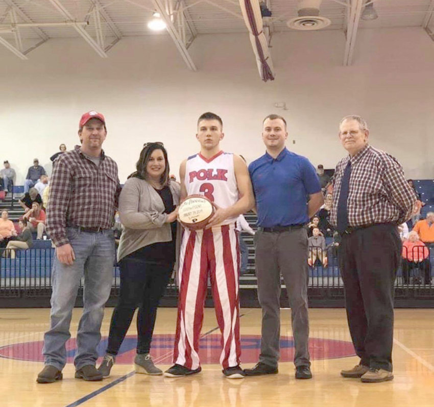 """POLK COUNTY WILDCATS junior basketball player Luke Burrows scored his 1,000th career point Jan. 28 against Midway. """"Luke is an outstanding young man on and off the court. All of his hard work and effort that he puts into this game is paying off. He is extremely deserving,"""" said head coach Jon Tucker. From left, Russ Burrows, father; Farrah Burrows, mother; Luke Burrows; Jon Tucker, wildcats head coach; and Ron German, PCHS principal and athletics director."""