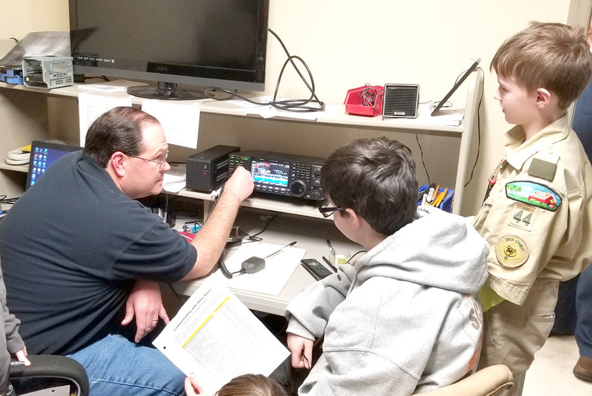 Jessie Rogers W4JUU provides instruction before two members of Troop 44 Boy Scouts of America from Wesley Memorial United Methodist Church made their first on-the-air contacts Saturday at the Cleveland Amateur Radio Club. Members of Troop 44 were pursing their amateur radio merit badge.