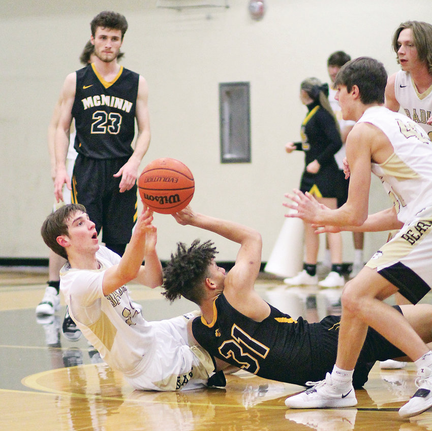 BRADLEY CENTRAL'S Mason Rothwell (on floor) pushes the ball to teammate Aiden McClary (40) over McMinn County's Tyler Peel (31)  in the second half of the District 5-AAA consolation game Tuesday, at Soddy-Daisy High School.
