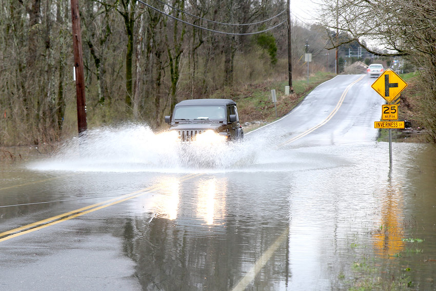 A JEEP is driven through a flooded portion of Candies Lane N.W., after thunderstorms drenched the area Tuesday night. A road project is planned for this summer, which will raise a portion of the road where rain and creek water pool.