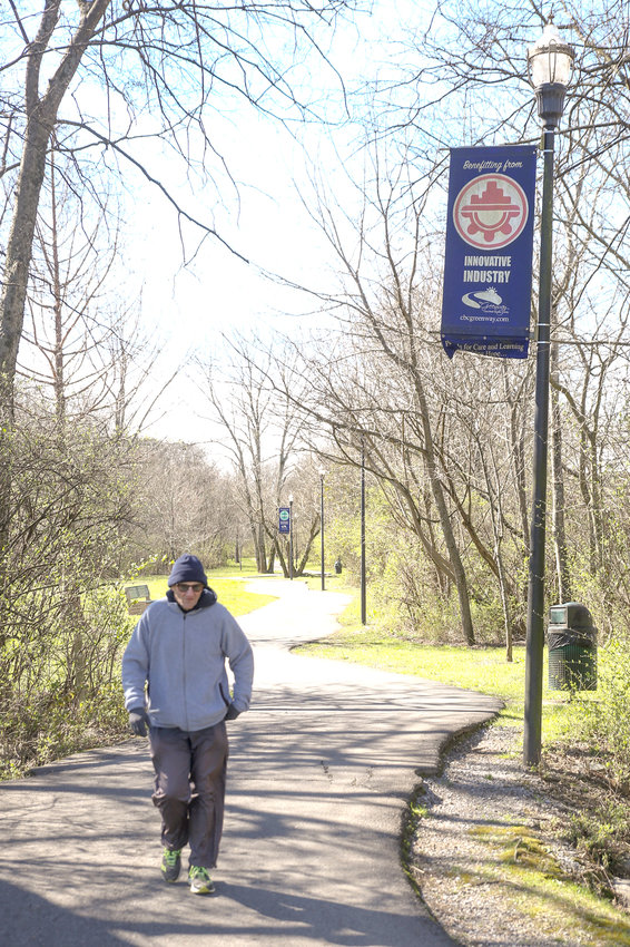 """A CLEVELAND MAN enjoys an early morning walk on the Cleveland/Bradley County Greenway. To his right is a banner attached to a decorative light pole that displays the name of a sponsor and the """"Innovative Industry"""" category that it supports. Friday is the deadline for leasing the two-year banners. Cost is a one-time fee of $350 for the two-year cycle."""