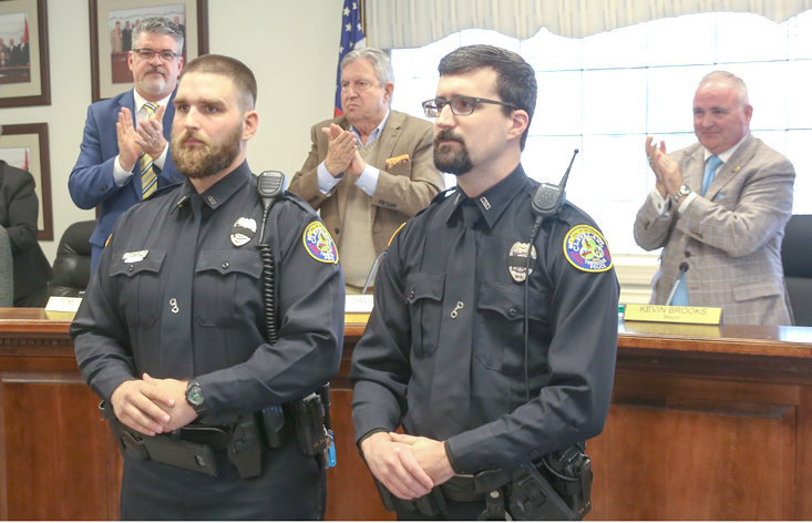 OFFICER MATT SHARP, left, and Officer Geoffrey Humberd stand in front of the Cleveland City Council at the Monday session as they are honored for their life-saving efforts on a recent call. The officers were recognized with applause and a standing ovation during the meeting. From left are Councilman Tom Cassada, Sharp, Councilman David May, Humberd and Mayor Kevin Brooks.