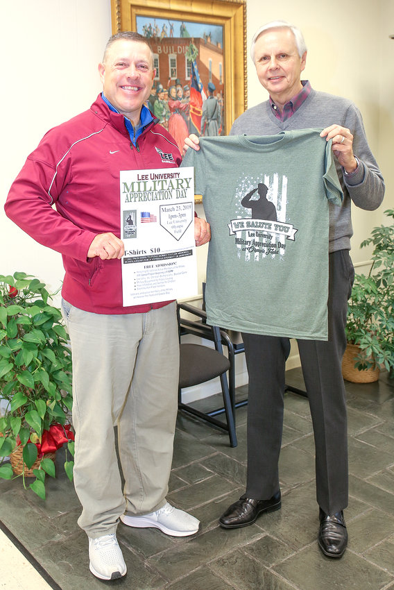 "MARK BREW, left, head coach of the Lee University Flames baseball team, and Ralph Baldwin, publisher of the Cleveland Daily Banner, display the T-shirt commemorating 2019 Military Appreciation Day. Featuring the ""We Salute You"" event theme, the T-shirts can be purchased at the Bank of Cleveland main office downtown, at the Cleveland Daily Banner offices on 25th Street and on the Lee University campus. Price is $10."