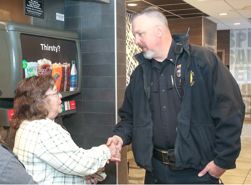 CLEVELAND RESIDENT Christine Lay shakes hands with Lt. Matt Jenkins during the local Coffee with a Cop event held Thursday at McDonald's off APD 40. During the meet-and-greet, coffee and McCafe Donut Sticks were served free to customers who dropped by to spend time with CPD officers.