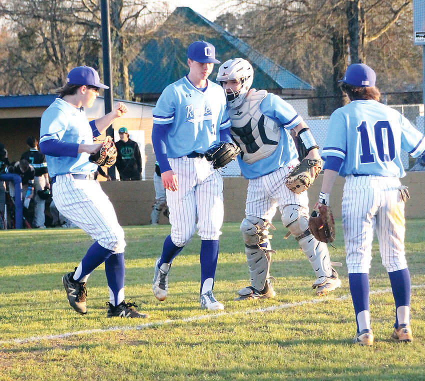 CLEVELAND HIGH hurler Asa Blake, second from left, is congratulated by teammates Sam Wyrick, left, catcher Ryan Lee and Jonathan Powers (10) as he comes off the mound between innings of Tuesday's District 5-AAA battle with East Hamilton at Raider Field.