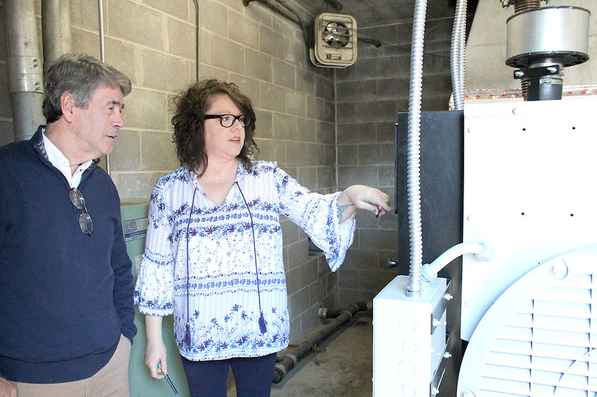 BILL WINTERS, chairman of the Bradley County Commission's Juvenile Committee, listens as Juvenile Court Administrative Assistant Malita Shaver talks about the new generator at the juvenile detention center. The generator was paid for from the current fiscal year budget.