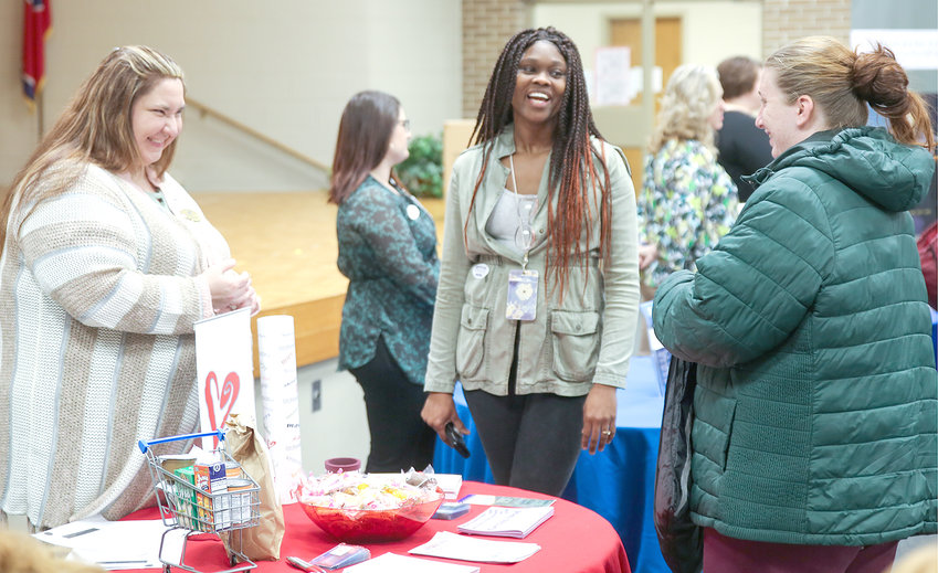 AMANDA DAVIS of The Caring Place, left, and Erica Sheppard, from Head Start, center, speak with Community Services Fair attendee Crystal Hutto on Tuesday.
