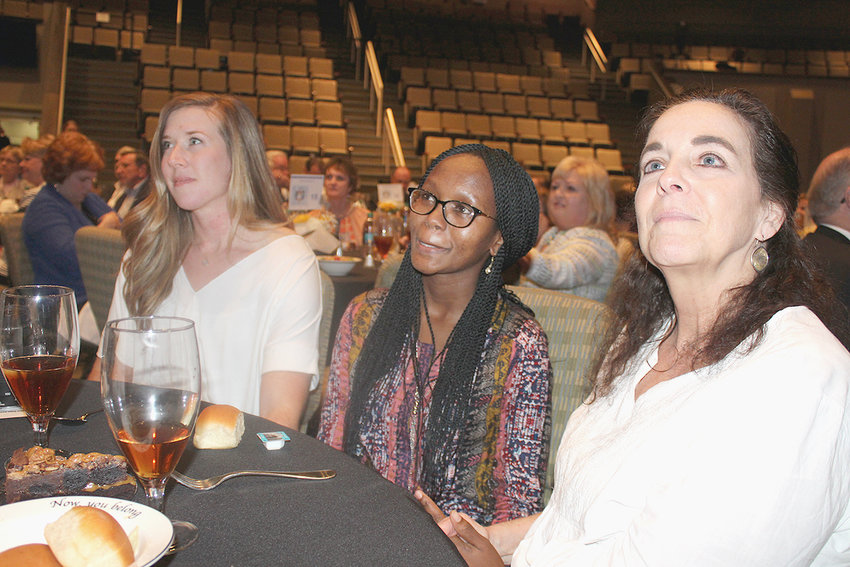 MERCY CHEPCHUMBA, center, a Lee University junior and former client of New Hope Pregnancy Care Center, holds back tears as a video showcasing her personal testimonial plays at Thursday night's New Hope banquet. From left are Breanna Hudson, Lee student and friend; Chepchumba; and Jan Wright, Lee student and friend.