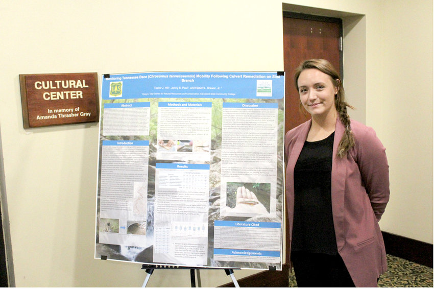 TAELOR HILL, a forestry, wildlife and fisheries program student at Cleveland State Community College, stands beside a poster that describes field research she conducted regarding population levels of the Tennessee Dace — a fish native to East Tennessee.