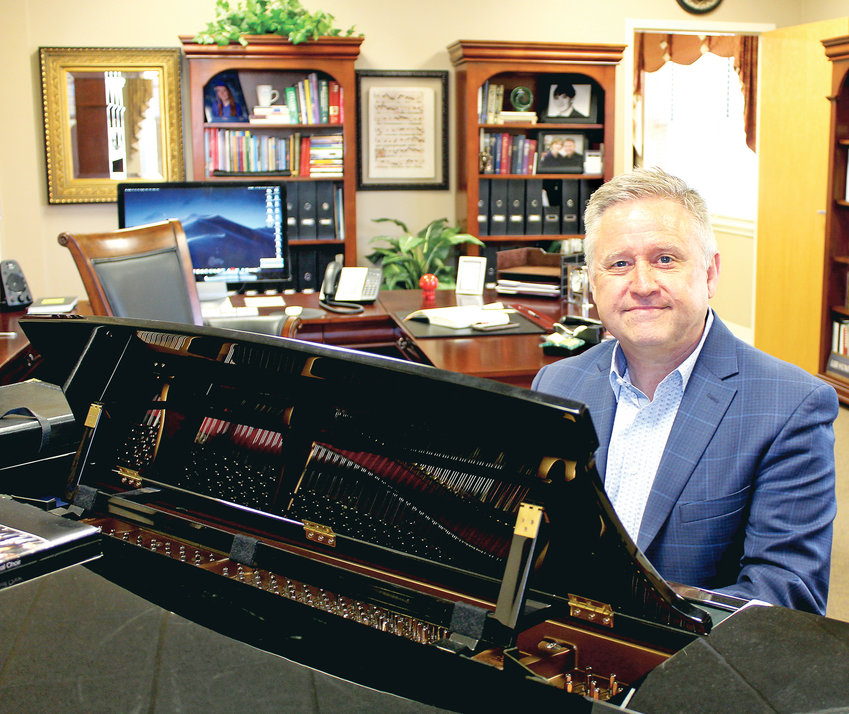 DR. WILLIAM GREEN, dean of the School of Music at Lee University, plays a hymn on the piano in his office. Music has been a major part of his life since junior high.