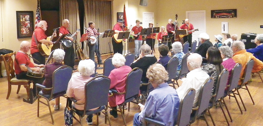 SPREADING the joy of music was the First United Methodist Church String Band, which gave a fun performance to the residents of Garden Plaza. The band is a loose-knit, just-for-fun group of new and experienced minstrels playing a variety of stringed instruments. Members are, from left, Mike Travis on resonator guitar, Dave Rhyme on guitar, Tom Dye on flat guitar, Dave Wright on banjo, Doug Greene on guitar, Nat Travis on mandarin, Elizabeth Kalabus on ukulele, Connie Wright on strum stick, Bill Swain on bass fiddle and Ken Jones on guitar.