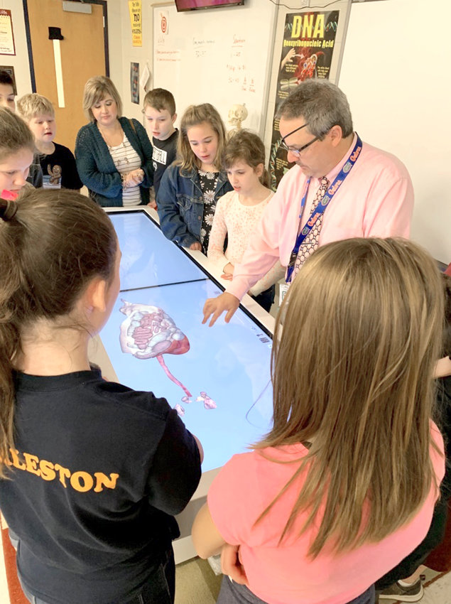 Bo Borders, science teacher at Walker Valley High School, shows elementary students the digestive system on the Anatomage Table.