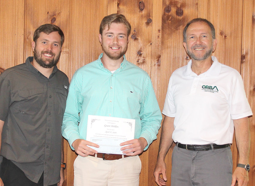 GRANT HOLDEN, center, is a Walker Valley High School senior who was recently awarded a $1,000 scholarship by the Ocoee Region Builders' Association for his excellent grades and school involvement. From left are Blake Allison, ORBA president; Holden, scholarship recipient; and John Proffitt, chairman of the education committee awarding the scholarship.
