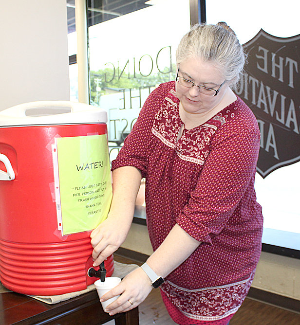 MONICA LUITHLE, social services coordinator for The Cleveland Salvation Army, fills a cup of water for a client at the hydration station in the office lobby. Free water is available from the hydration station, 9 a.m. to 4:30 p.m., Monday through Friday.