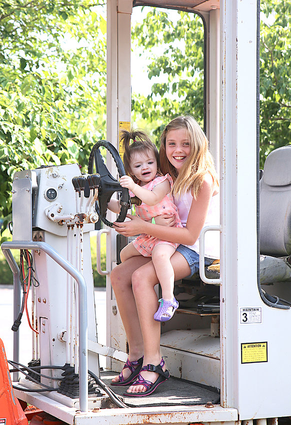 HANNA MOODY, seated, holds Esmeralda Headrick as they take control of a Road Grader at the Big Truck Roundup on Saturday. Hanna's parents are Jamie and Jeri Moody, and Stephanie Kruse and Esmeralda's parents are Tanner and Tiffany Headrick.