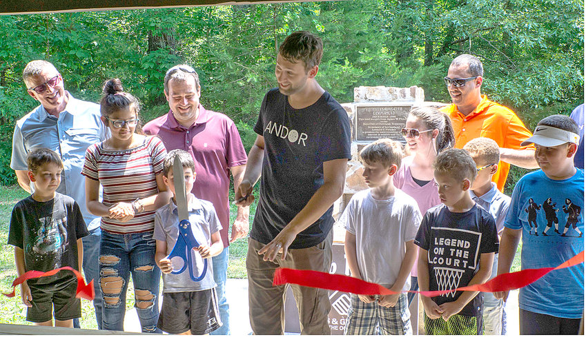 A RIBBON CUTTING was recently held for the Boys and Girls Clubs of the Ocoee Region's Camp Fletcher. Andor program director Mike Stoess cuts the ribbon with help from children. In back, from left, are Roger Pickett of Murmaid Mattress, George Gray (BGCOR Board President) and Sherwin-Williams representative Justin Bonner.
