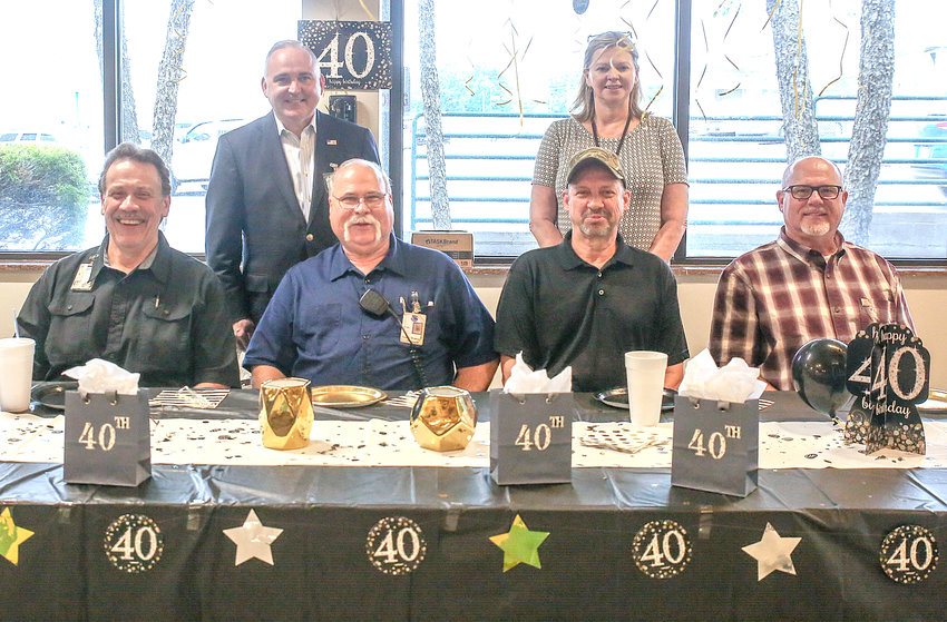 PEYTON'S SOUTHEASTERN INC. celebrated its 40th year of operation on Wednesday, and honored four of their employees who have been with the company since its inception. Front row, from left, are Bruce McDonald, Brian Gladson, Danny Womac and Chuck Ingram. Back row, from left, are Cleveland Mayor Kevin Brooks and Peyton's Southeastern Senior Supply Chain Manager Angie Freeman.