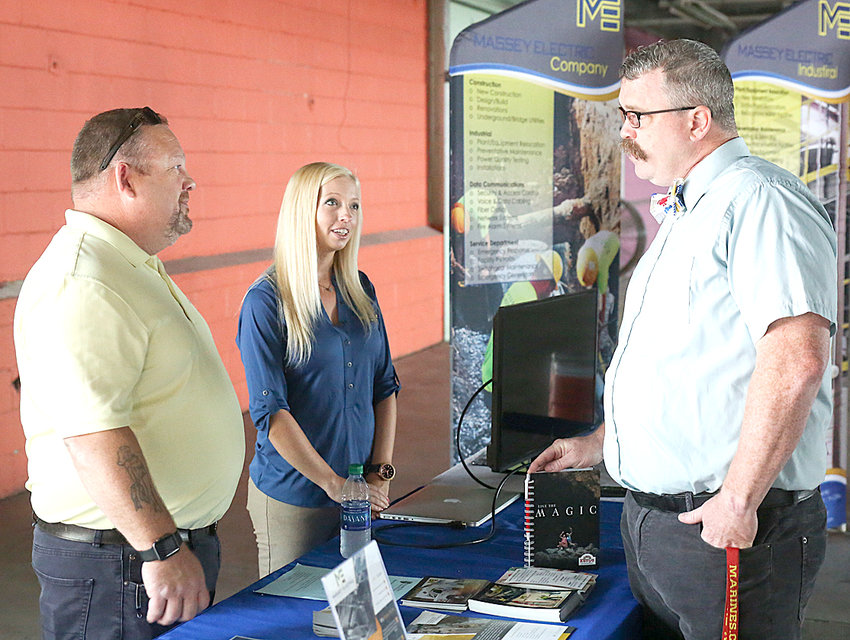 WHILE ON A GUIDED tour, Dusty Strickland, assistant principal at Pleasant Valley Innovations in Chatsworth, Ga., right, speaks with Thomas Goins, left, and Jeanette Beaverson from Massey Electric about their plans at the PIE Center.