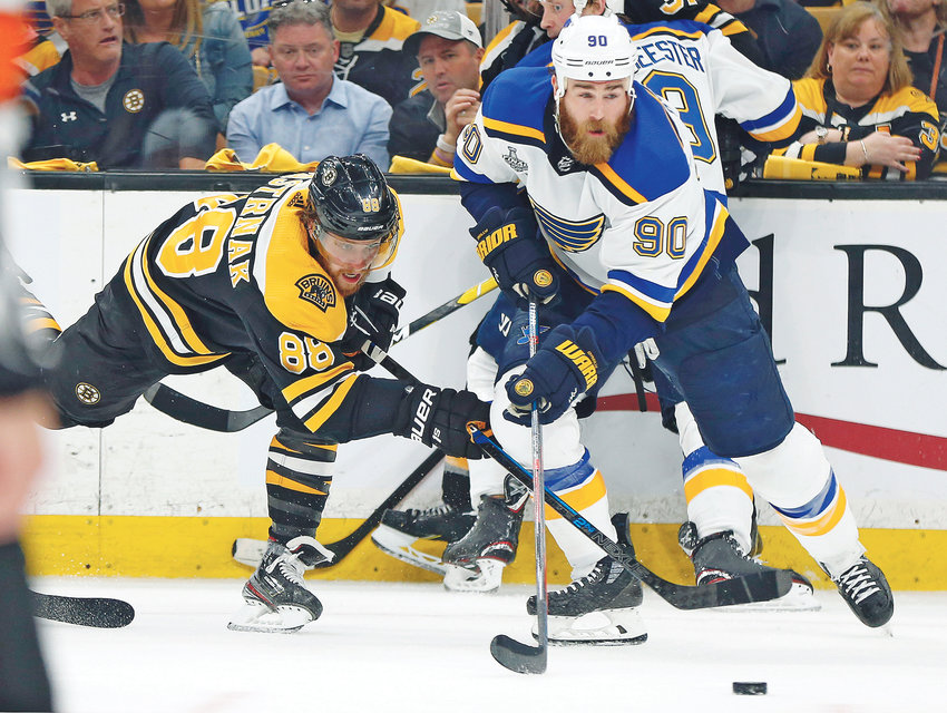 ST. LOUIS BLUES' Ryan O'Reilly (90) moves the puck away from Boston Bruins' David Pastrnak, left, in the second period of Game 7 of the Stanley Cup Final Wednesday, in Boston.