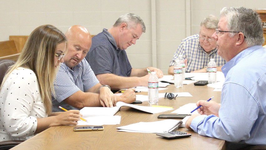 FINANCE COMMITTEE members Erica Davis, from left, County Commission Chairman Johnny Mull, Finance Committee members Mike Hughes and Louie Alford, and Finance Committee Chairman Milan Blake double-check budget numbers during Thursday's meeting.