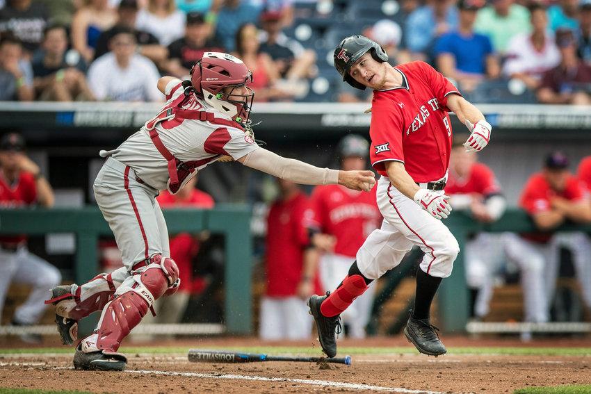 Arkansas catcher Casey Opitz, left, tags Texas Tech's Dylan Neuse after a dropped third strike during an NCAA College World Series game Monday, June 17, 2019, in Omaha, Neb. (Brendan Sullivan/Omaha World-Herald via AP)