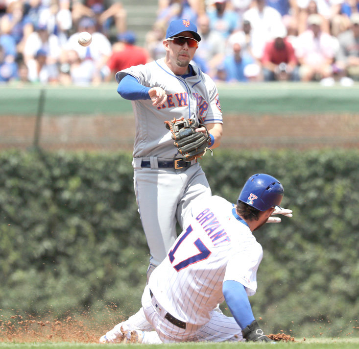 NEW YORK METS second baseman Jeff McNeil throws out Chicago Cubs' Javier Baez at first after forcing out Kris Bryant at second in the first inning Saturday, in Chicago.