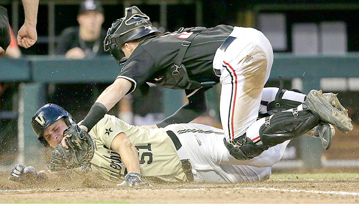 VANDERBILT'S JJ Bleday (51) scores past Louisville catcher Henry Davis on an RBI double by Ethan Paul in the ninth inning at the NCAA College World Series Friday, in Omaha, Neb.