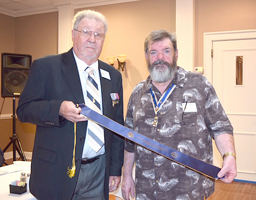 JOHN CLINES right, state commander Of the Tennessee SAR Color Guard, receives a streamer recognizing the color guard participation in Virginia'ss re-enactment of the 18th-century raid at Martin's Station from chapter Second Vice President Jerry Hjellum.