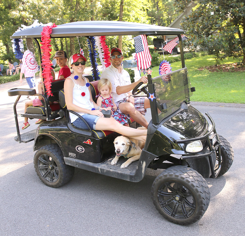 THE FORD FAMILY, complete with pup in tow, rode around in style during the annual Ridgewood subdivision parade on the Fourth of July.