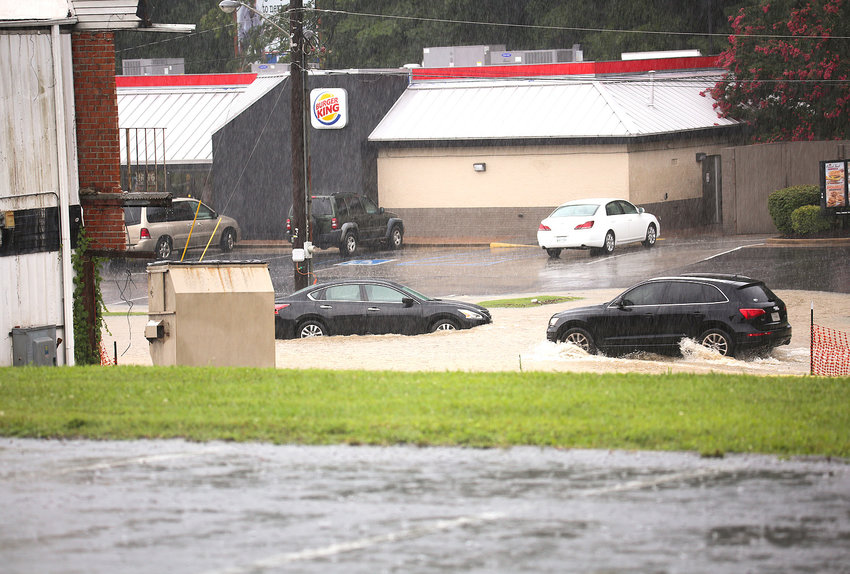 AN SUV PASSES THROUGH flood waters along Little Street N.W., while a car sits trapped in the water. The side street is just off 25th Street and runs between a Burger King restaurant and the Economy Inn.