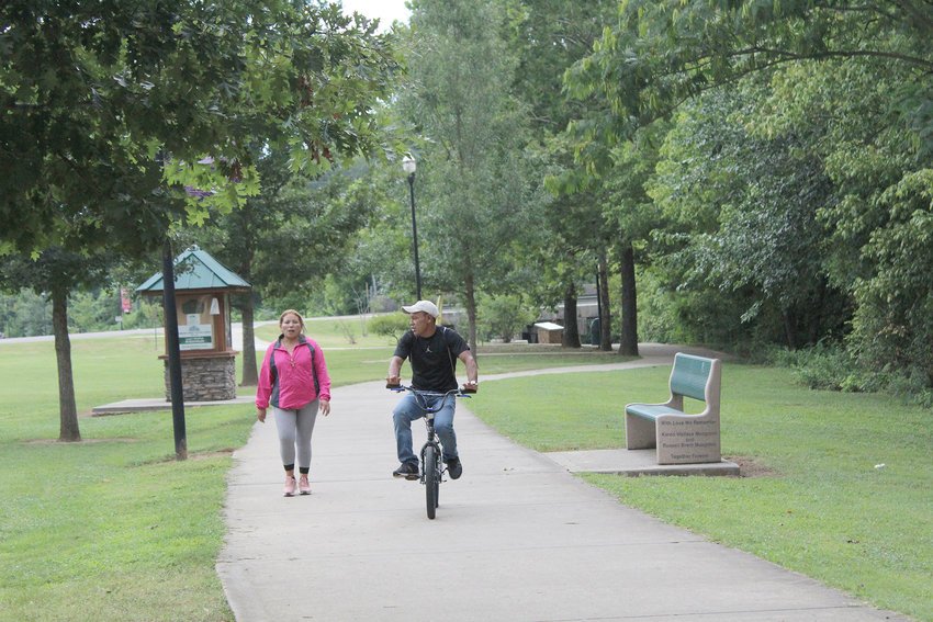A WOMAN walks beside a man riding a bike late Sunday afternoon along a stretch of the Cleveland/Bradley County Greenway near Greenway Park.