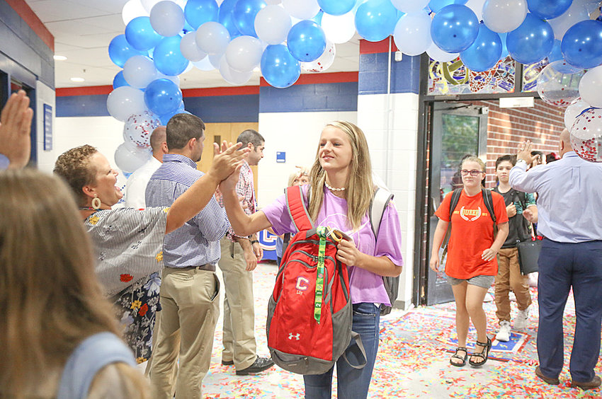 LILY O'BRYAN, center, high-fives teacher Ashley Meagher as she arrives for her first full day of the school year at Cleveland Middle School.