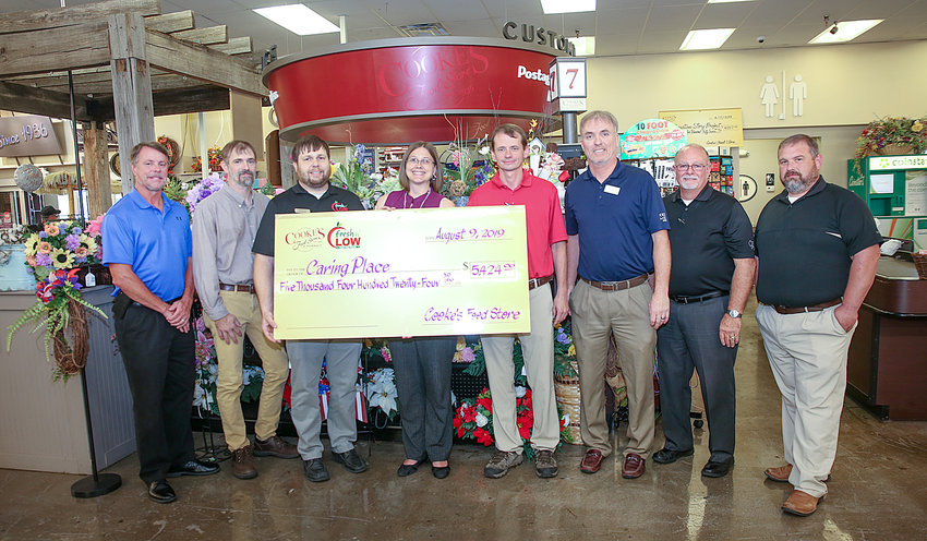 """REPRESENTATIVES FROM COOKE'S FOOD Store met on Friday to present Corinne Freeman of The Caring Place with a check for $5,424 raised through donations by Cooke's Food Store customers. Partnering with The Caring Place for the annual """"Hunger Doesn't Take a Vacation"""" food drive, Cooke's also donated 9,000 pounds of food and 627 $5-bags of non-perishable food items purchased by customers. From left are Jim Phiropoulos, Lynn Phillips, Russell Viola, Corinne Freeman, Tim Gaddis, Keith Scott, Tom Harris and Chris Farrar."""