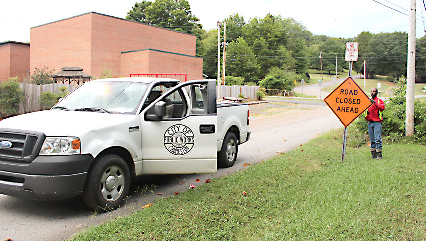 "CHARLESTON Street Supt. Melvin Graham, right, was busy just before darkness Tuesday evening removing the final ""Road Closed"" sign along Worth Street in Charleston. The poor condition of the roadway forced city authorities to close the street about a month ago, which has been a disruption to traffic to and from Charleston Elementary School."
