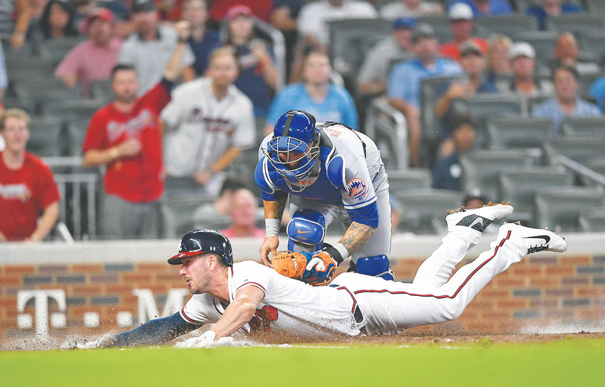 ATLANTA BRAVES' Matt Joyce slides safely into home as New York Mets catcher Wilson Ramos tries to make the tag in the seventh inning Wednesday, in Atlanta.