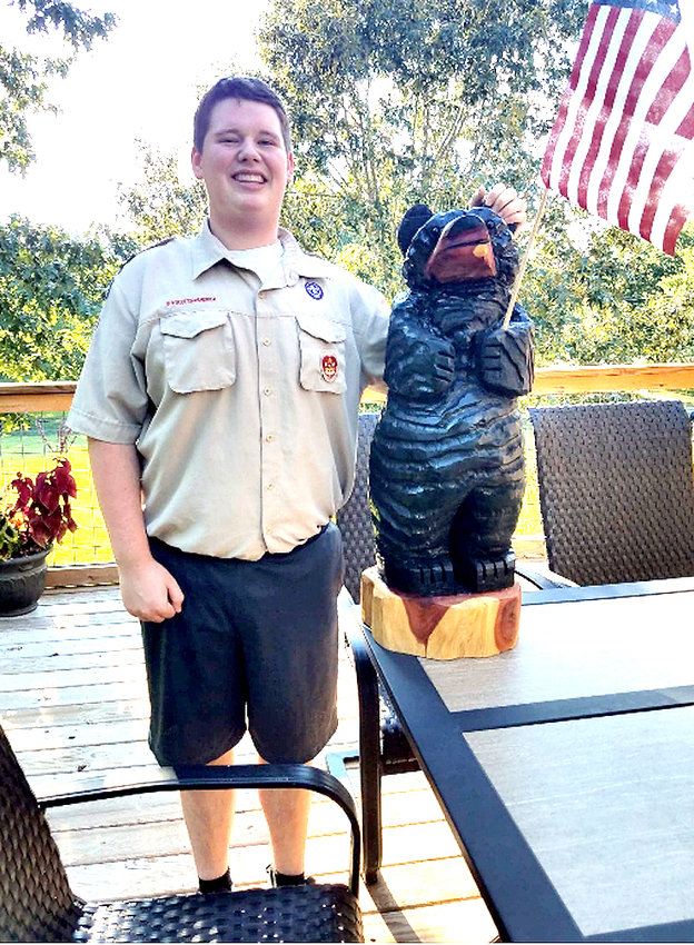 CASEY NEEPER, a Boy Scout with Troop 44 in Cleveland, stands beside a carved wooden bear he is auctioning to raise money to support his Eagle Scout service project.