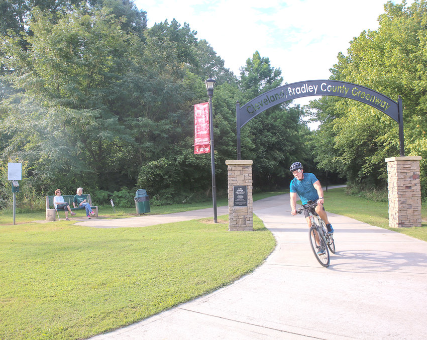 GREENWAY USERS who start their journey from the popular Mohawk Trailhead are now greeted with a welcoming, and decorative, gateway arch thanks to a donation by Manufacturers Chemicals as part of the company's 100th anniversary celebration. Here, a bicyclist makes his way off the greenway, while two walkers take a brief rest on the bench at left.