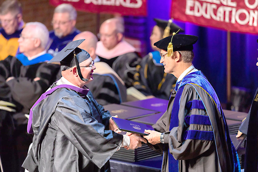 ANDY WATTENBARGER, Lee University's first graduate in the online criminal justice program receives his diploma from Dr. Paul Conn, Lee's president.