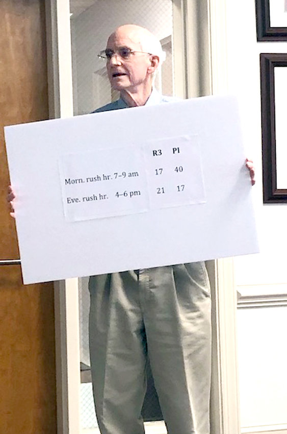 GEORGETOWN ROAD/Highway 60 area resident Roger Schmurr holds a sign that shows how a rezoning of residential properties located between Kimberly Drive N.W., and Weston Hills Drive N.W., from R3 Multi-family Residential to PI Professional Institutional, would result in increased traffic congestion.