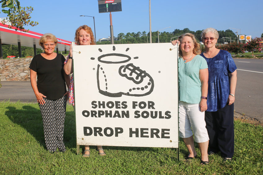 SHOES FOR ORPHAN SOULS is now more than halfway through the August 2019  drive, and the Cleveland Daily Banner is one of 43 drop-off locations. Displaying the front-lawn sign at the Banner offices are, from left, newspaper employees Crissy Dillard, Kathy Payne, Sheena Meyer and Vicky Guy.