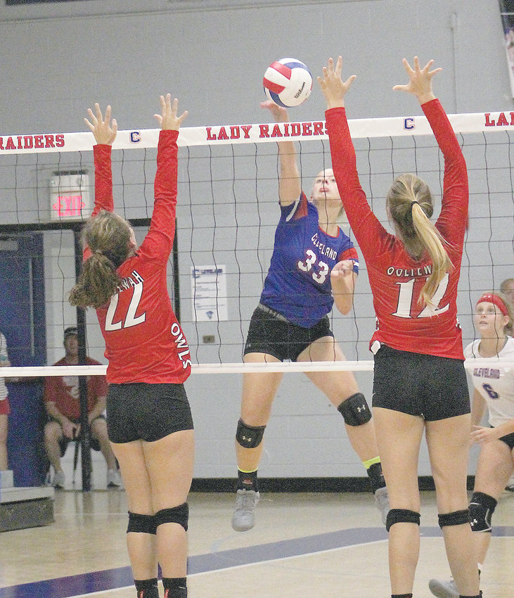 LADY RAIDERS outside hitter Joy Douglass (33) blasts a kill between a pair of Ooltewah defenders during a District 5-AAA volleyball matchup Thursday, at Cleveland.