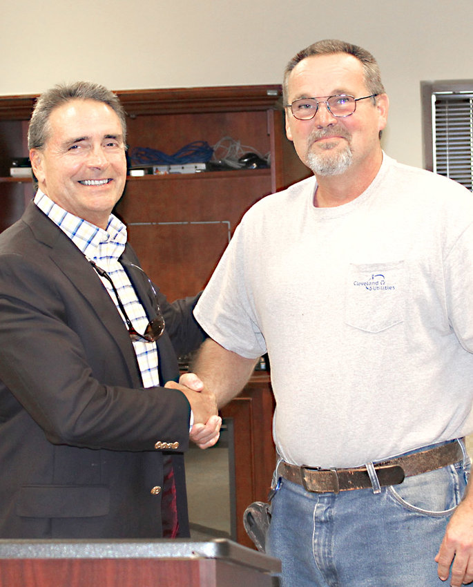 RETIRING CLEVELAND UTILITIES employee Doug Wilson, right, is congratulated by CU President and CEO Tim Henderson during a meeting of the board of directors Friday at the Tom Wheeler Training Center. Wilson has worked at CU since 1999.