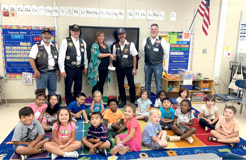 The American Legion Riders Post 81 of Cleveland presented a check for $125 to Claudia Parker, a kindergarten teacher at Mayfield Elementary, Friday. In the background, from left, are Daniel Sparks, Bob Taylor (assistant director), Claudia Parker, David Curler (director), and Jim Gruber. In the foreground are Parker's amazing students.