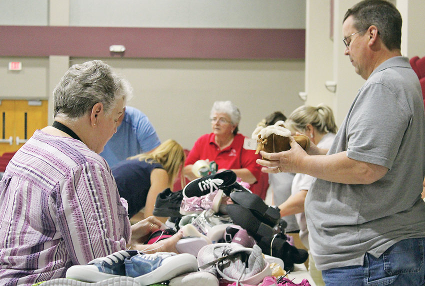 VOLUNTEERS WITH PARKWAY Baptist Church begin the packing party for Shoes for Orphan Souls on Thursday night at Westwood Baptist Church.