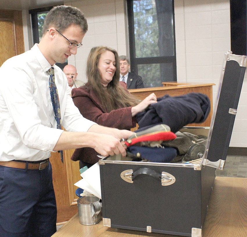 ELIJAH HAMMONDS, assistant curator of education for the Museum Center at 5ive Points, and Hope Vollm, curator of education, pack items into the Museum Center Trunk Shows' Civil War trunk following a presentation Monday to the Bradley County Commission. In the background are Commissioner Kevin Raper, left, and Commissioner Bill Winters.