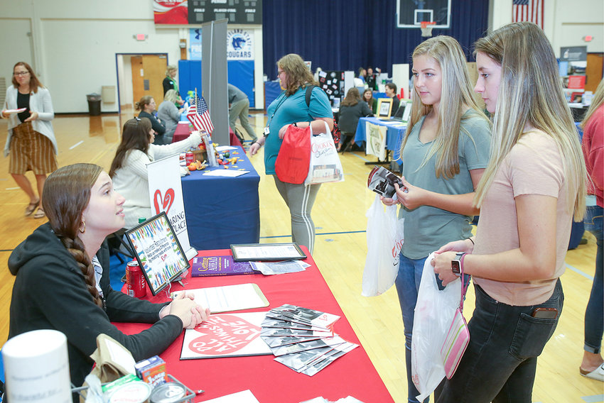 """LILY FREEMAN, community engagement coordinator for The Caring Place, left, speaks with Polk County High School students Emily Lanning and Ashlie Jones, right, during the   """"Make a Difference Now"""" Volunteer Expo Wednesday."""
