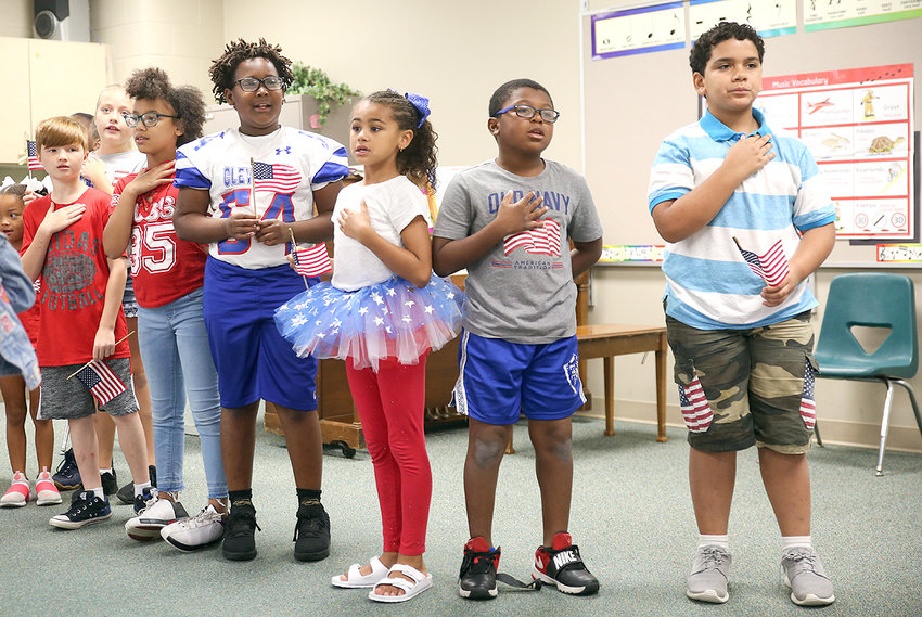 "SEVERAL HOMEROOM REPRESENTATIVES from across Blythe-Bower Elementary hold their hands to their hearts as they sing the ""Star-Spangled Banner"" on ""Star-Spangled Banner"" Day."