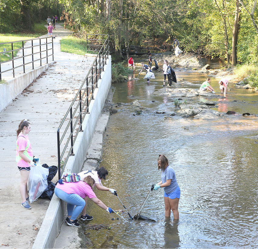 VOLUNTEERS clean trash out of Mouse Creek during a previous initiative held alongside the Cleveland/Bradley County Greenway. This portion of the greenway is located at the Willow Street extension which will be the site of Phase 6 of the linear park's growth.