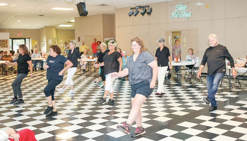 INSTRUCTOR JUDY ROGERS' line dancing group performs for the crowd in attendance at the Senior Center Celebration on Wednesday at the Bradley Cleveland Senior Activity Center. The line dancing group meets on Mondays at 1 p.m. at the center. From left are Susan Rackley, Pat Love, Suzanne Nerren, Robin DeFalco, Dianne Pesce, Madelaine Cofer, Jeannine Patterson and Bob Collier.