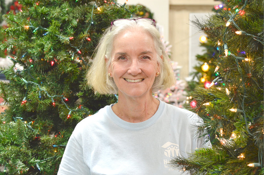 DEBORAH FLOWER, also known as the Christmas Lady, stands next to this year's lighted trees that are now decorated and on display at the Habitat of Cleveland ReStore. The trees are part of a fundraising effort for Habitat for Humanity to support their mission of providing proper housing for those in need.